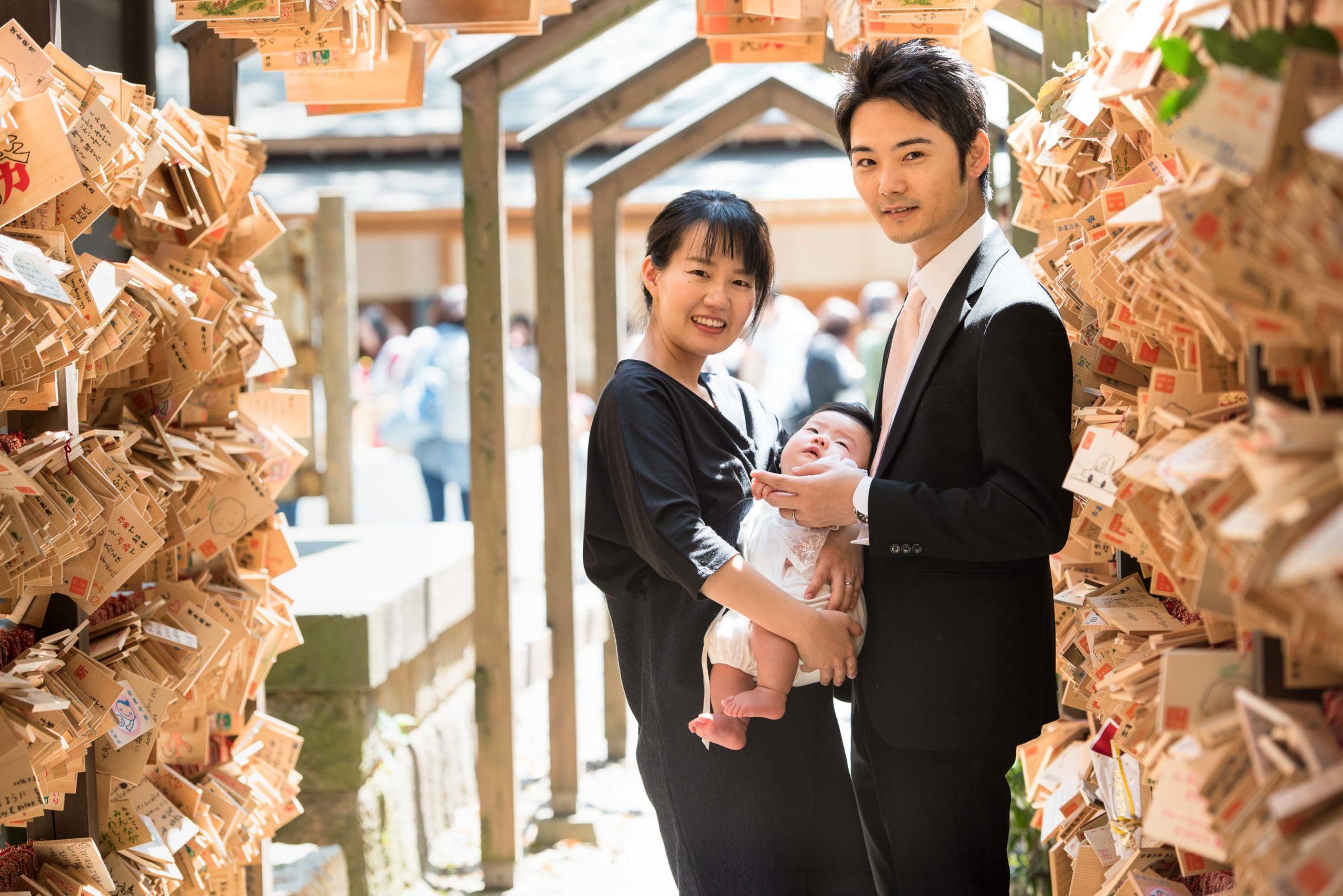 黒の洋服で赤ちゃんを抱く女性横に立つ男性