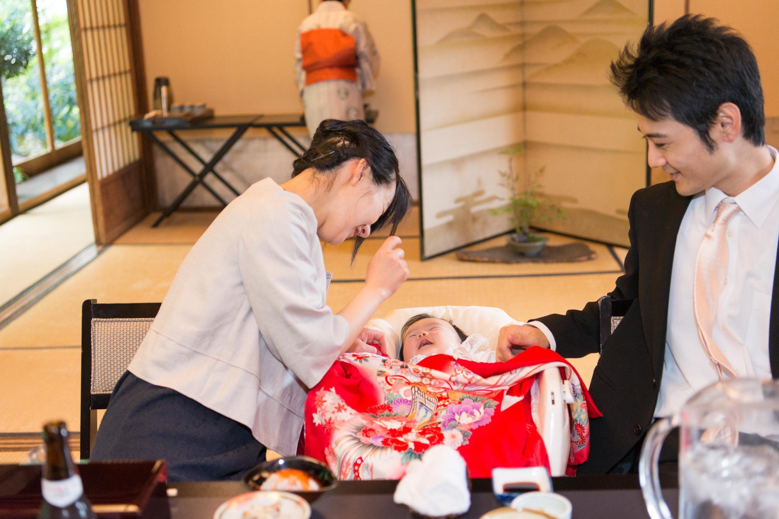 ベビーベッドに寝た赤ちゃんを覗き込む女性