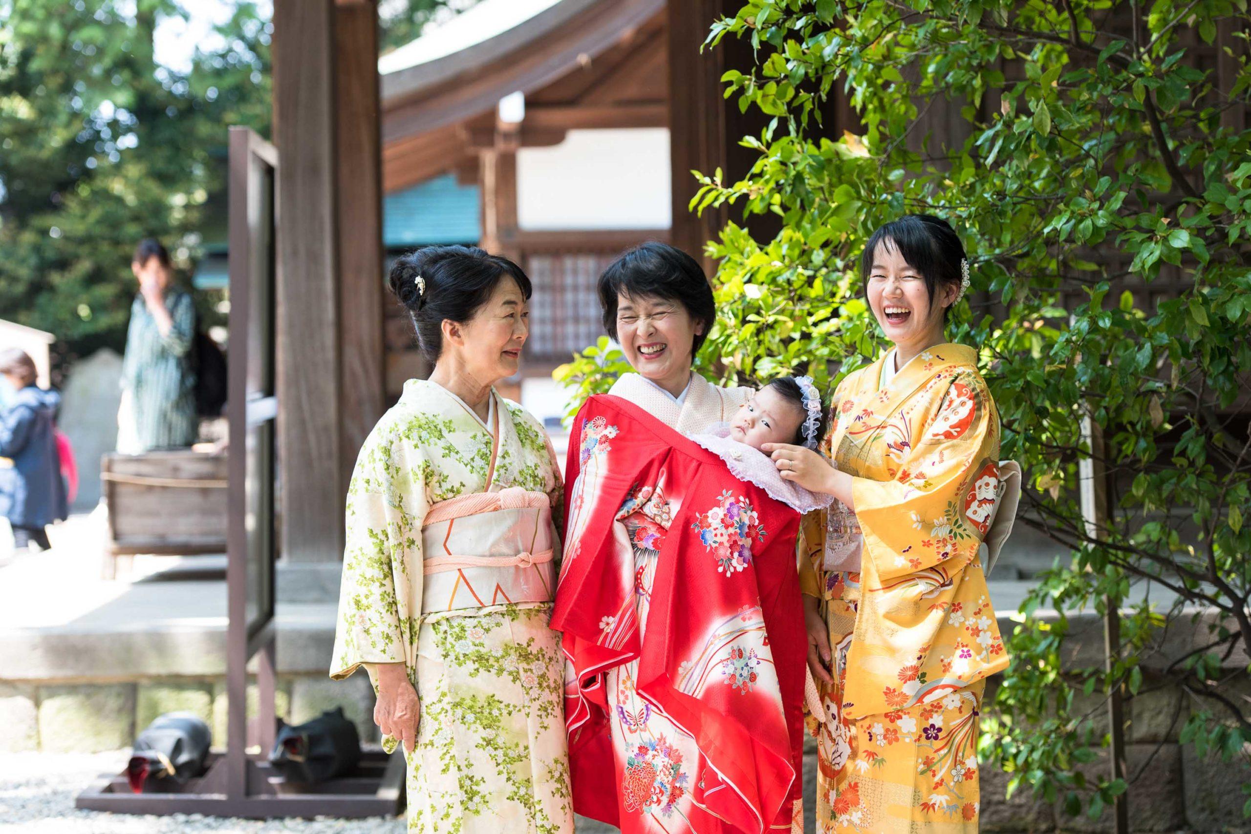 着物を着て並び笑う三人の女性真ん中の女性が赤ちゃんを抱いている