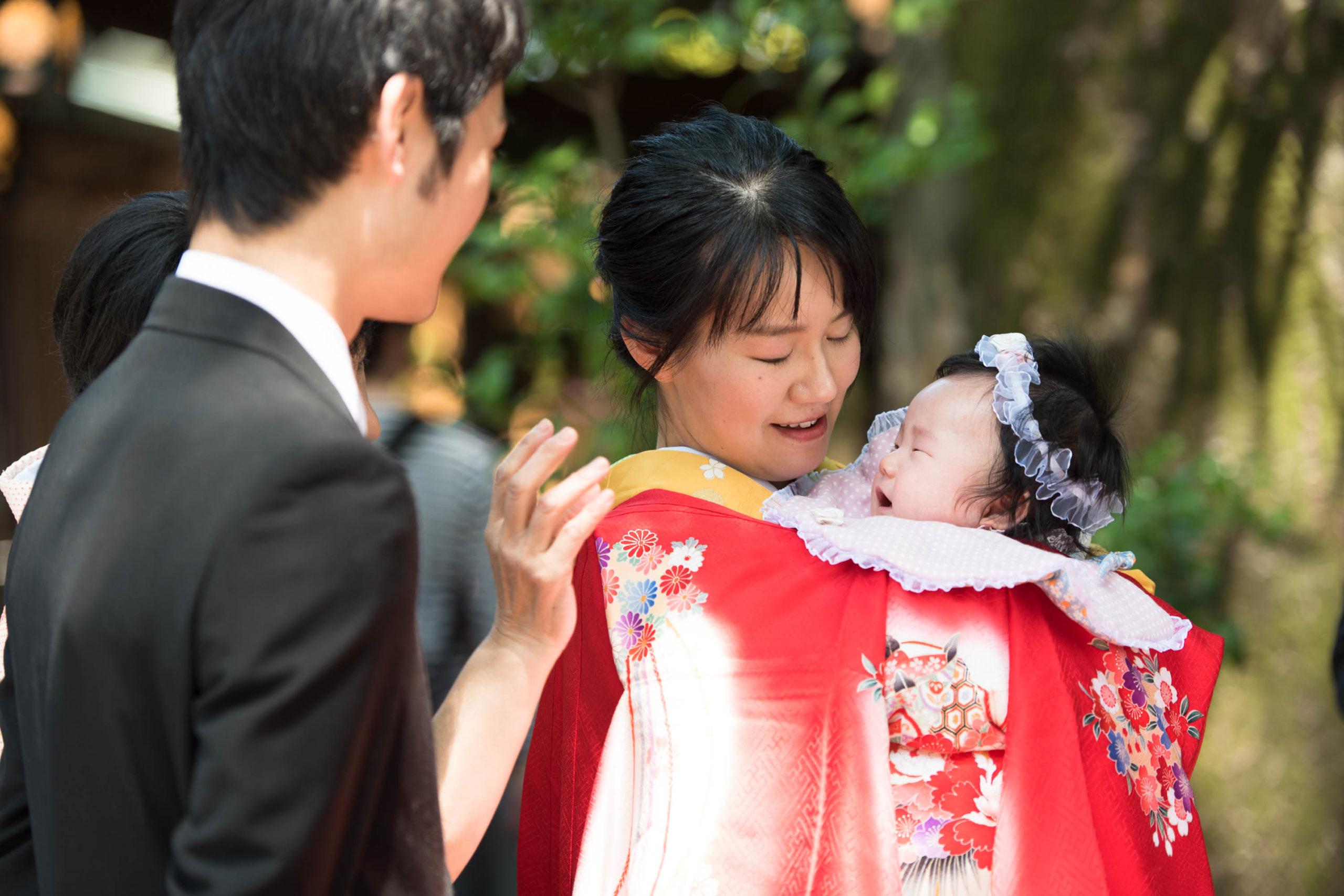 赤い掛け着を着た女性が赤ちゃんを抱いている