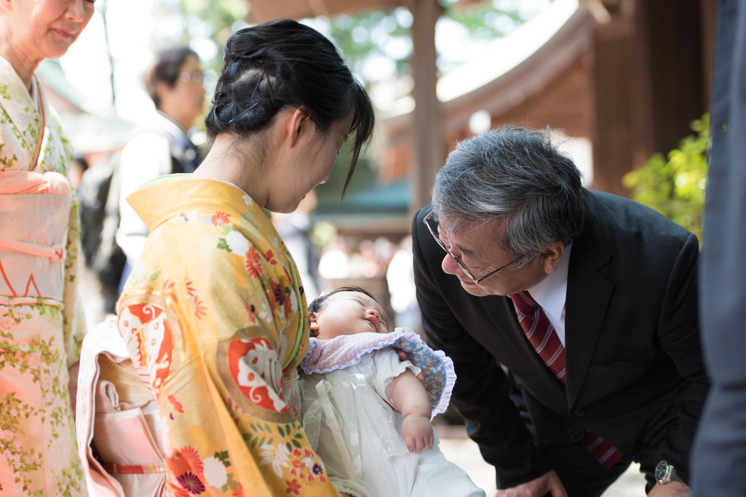 黄色の着物を着て赤ちゃんを抱く女性とそれをのぞき込むスーツ姿の男性