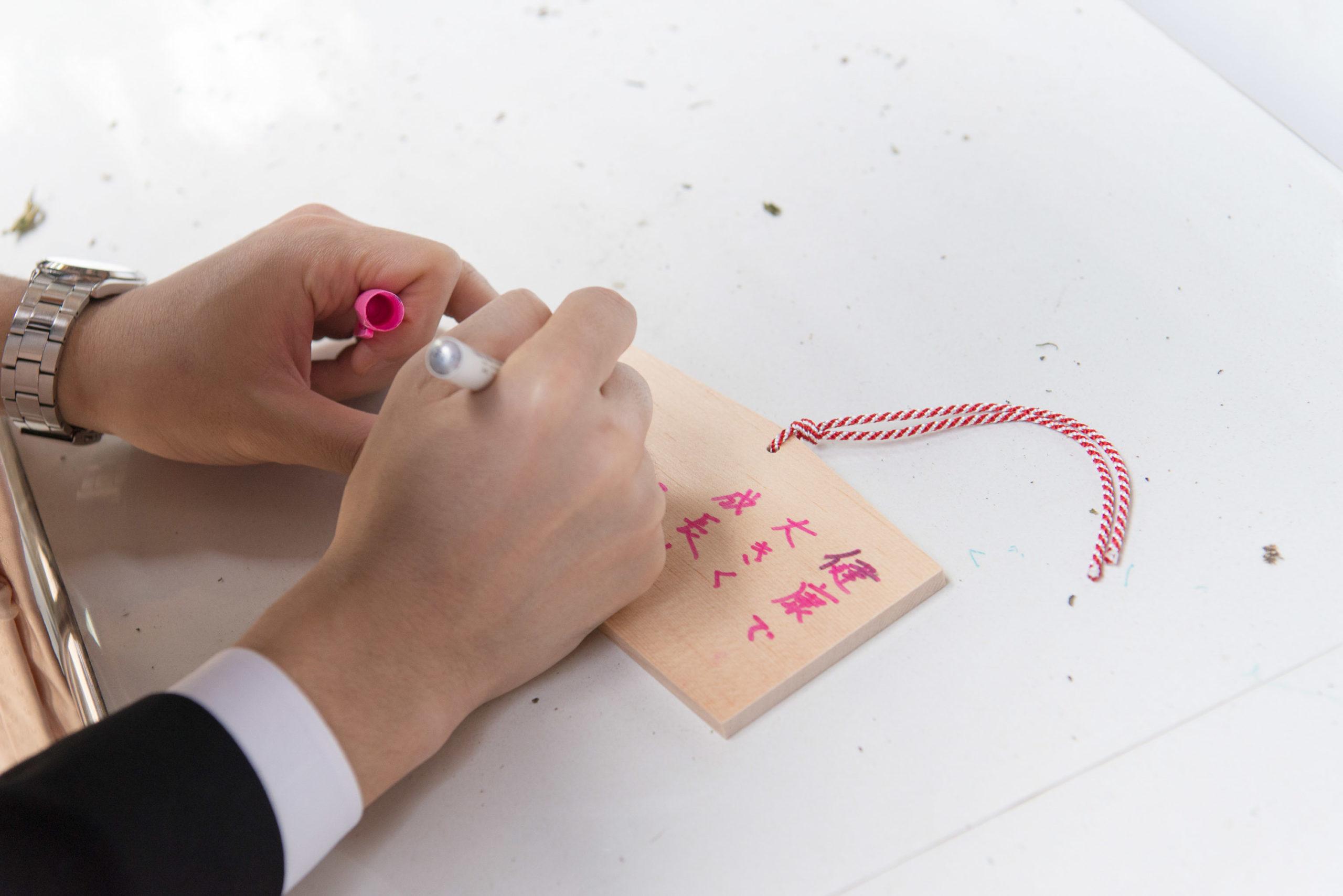 絵馬にピンク色のペンで願い事を書く手