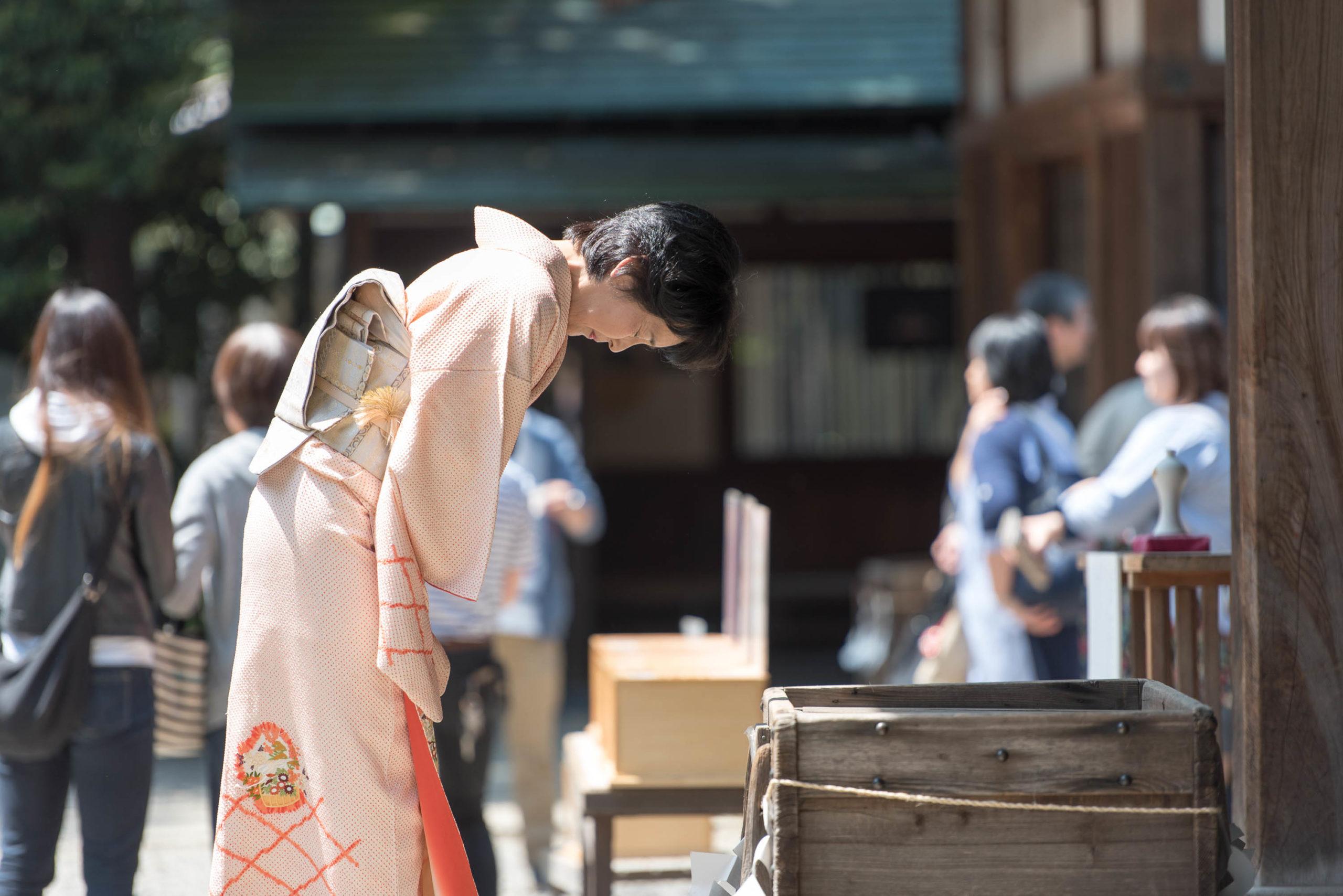 神社本殿の前で一礼するピンク色の着物を着た女性