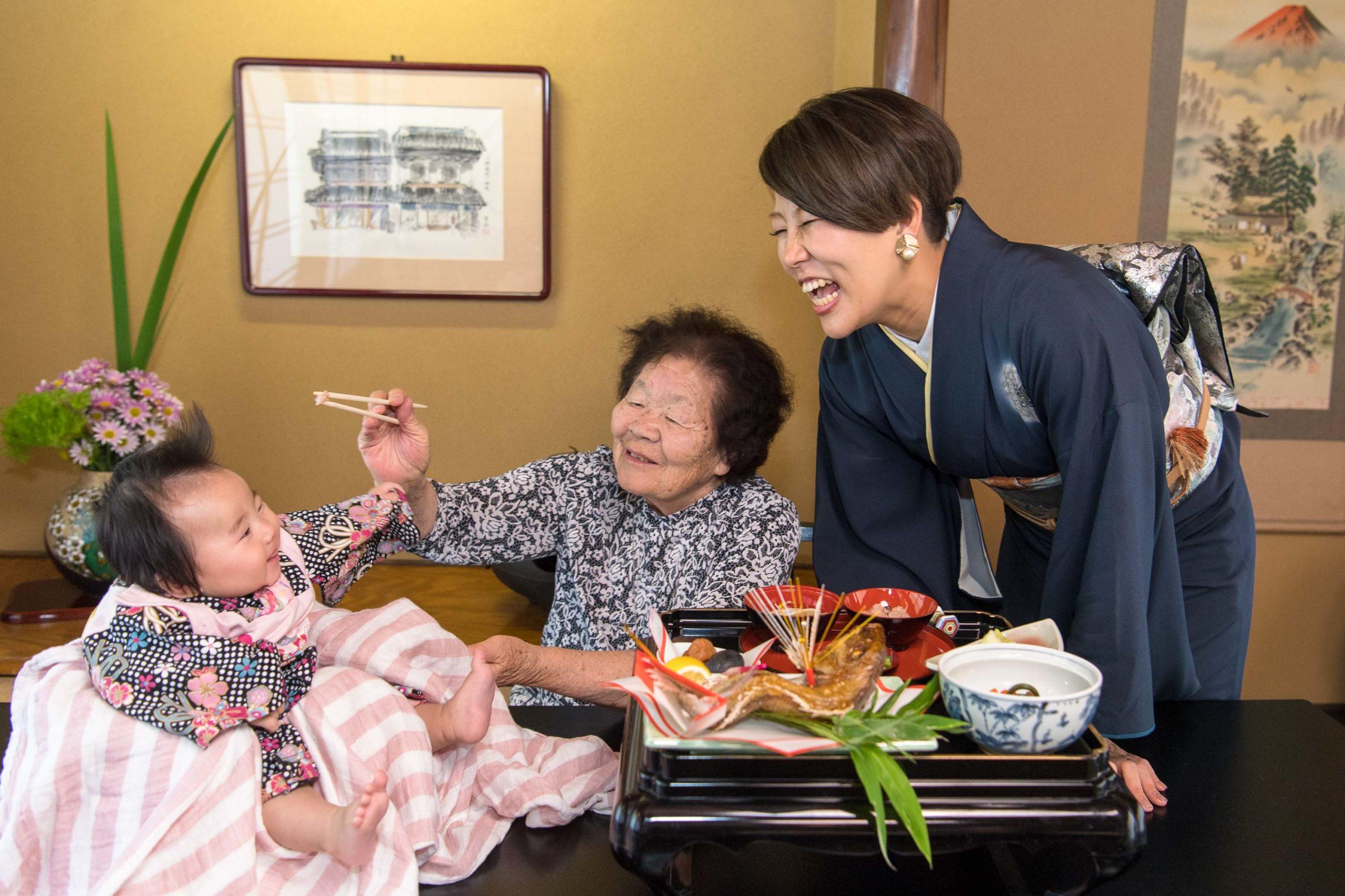 うなぎのいちにやの個室でお食い初めをするおばあちゃんと和服姿の女性