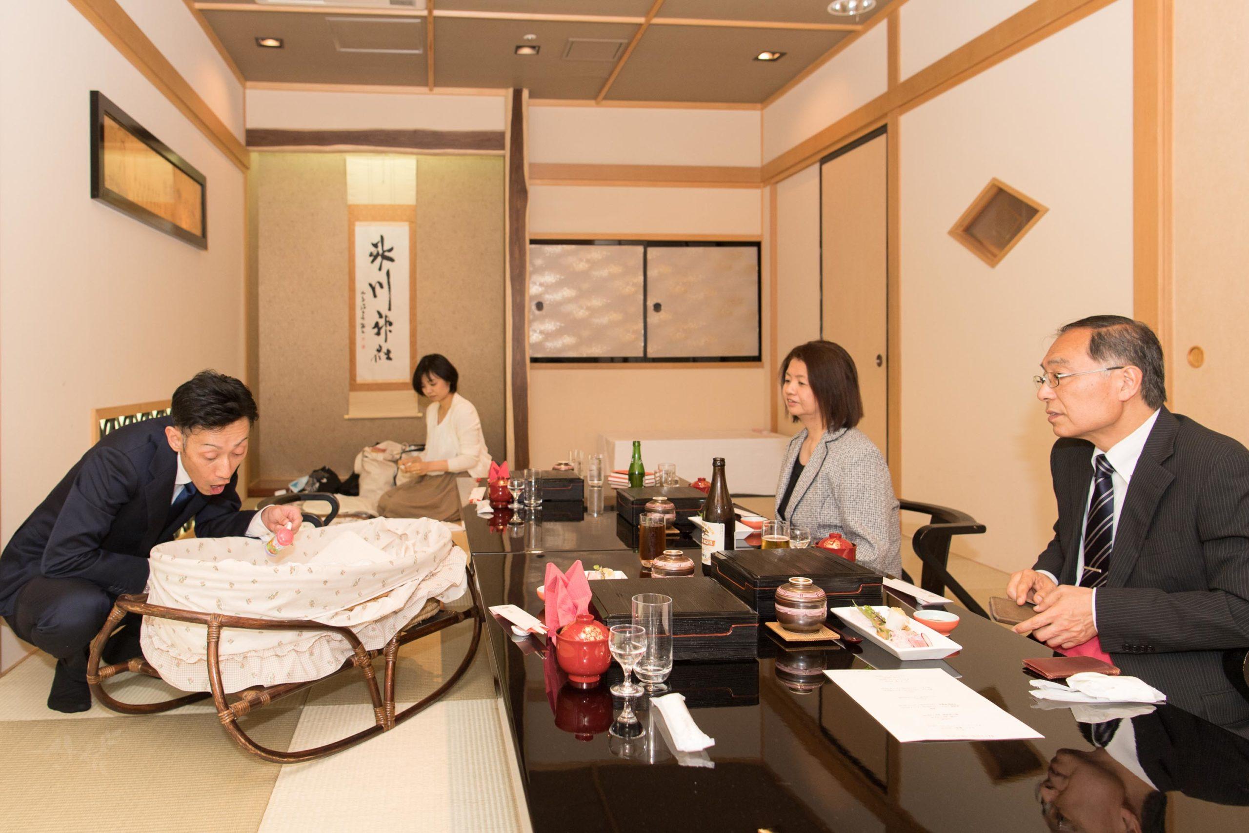 和室で大人4人の食事風景