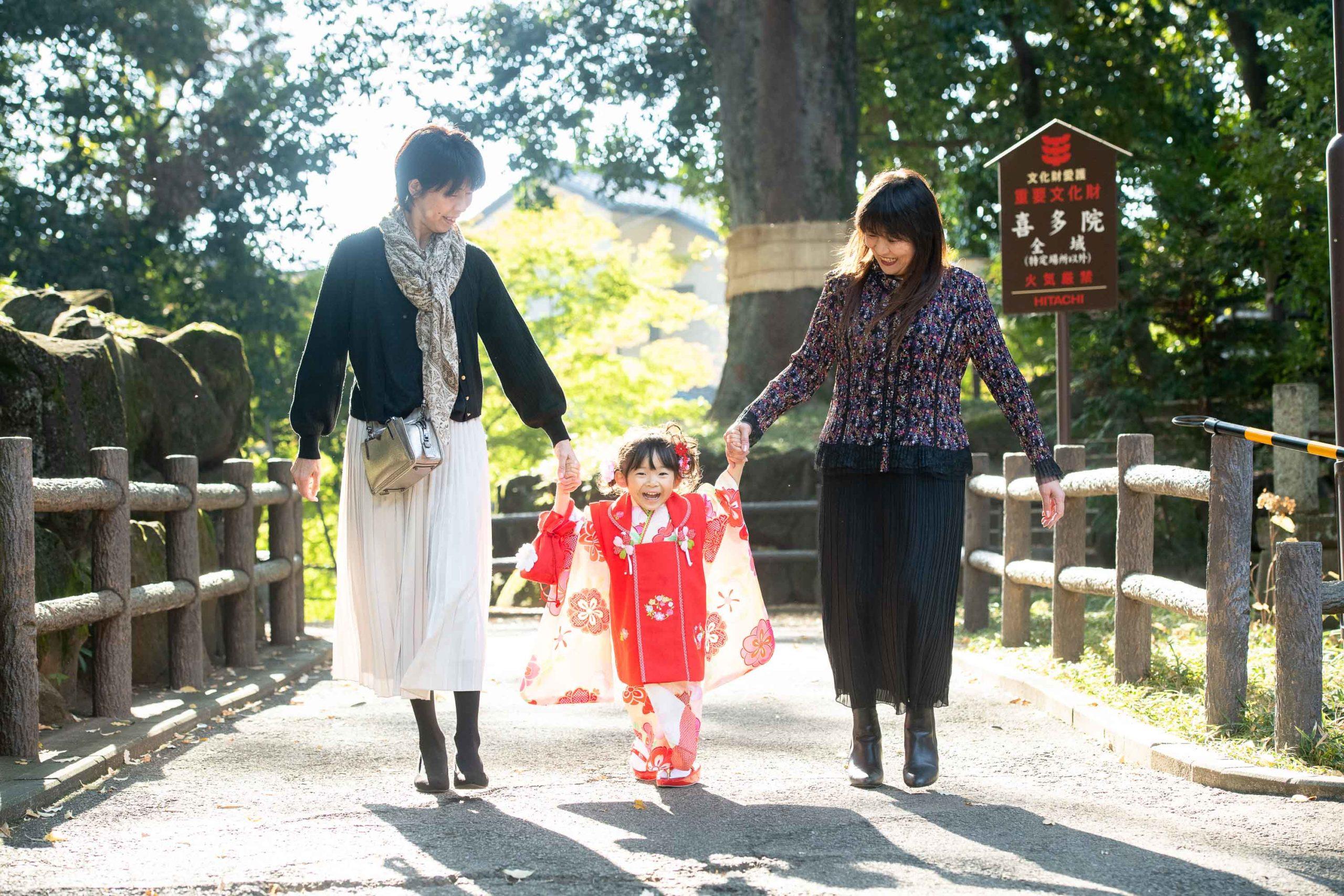 二人の女性に手をひかれる着物を着た小さな男の子と女の子