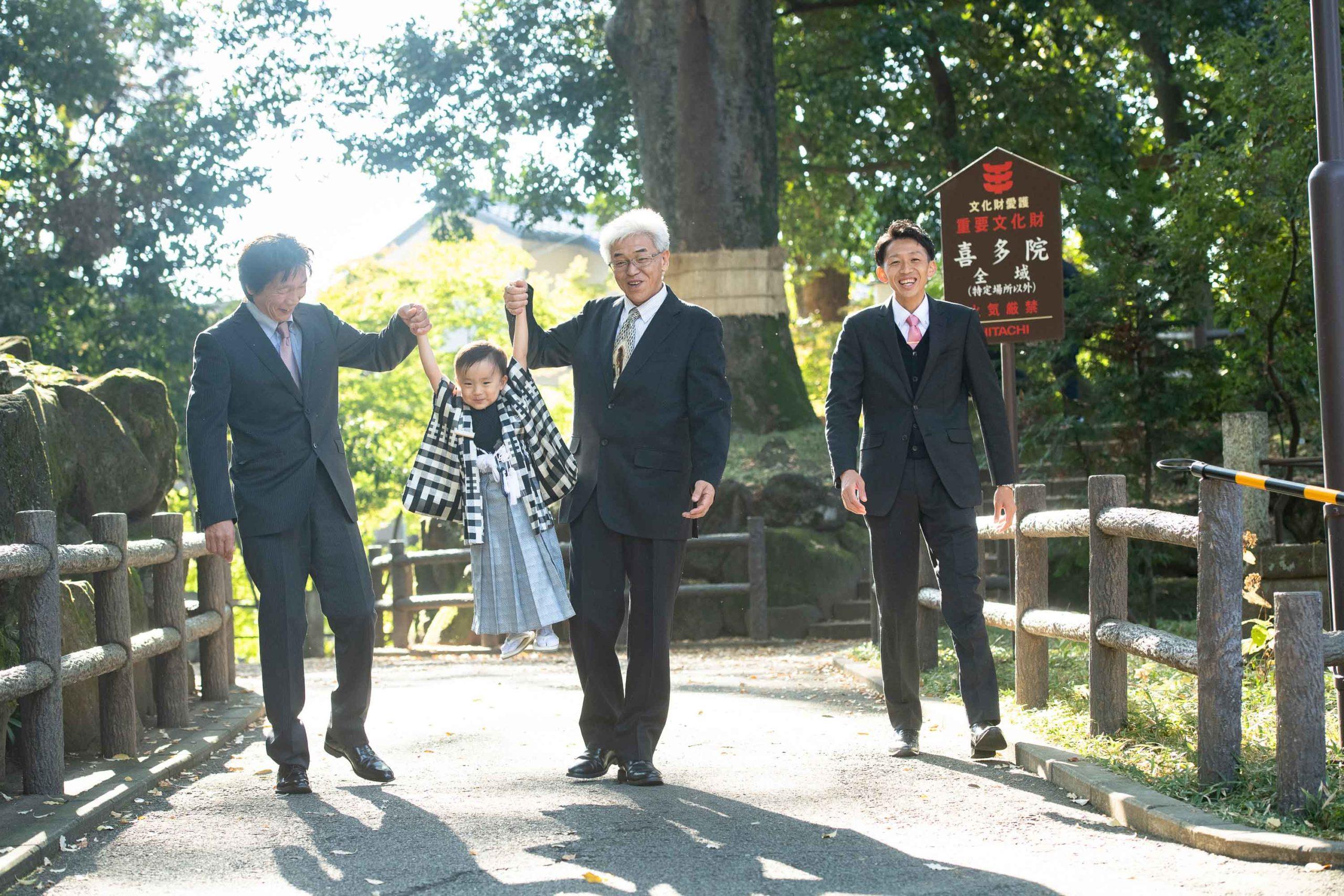 二人の男性に持ち上げられる着物姿の男の子と横に歩く男性