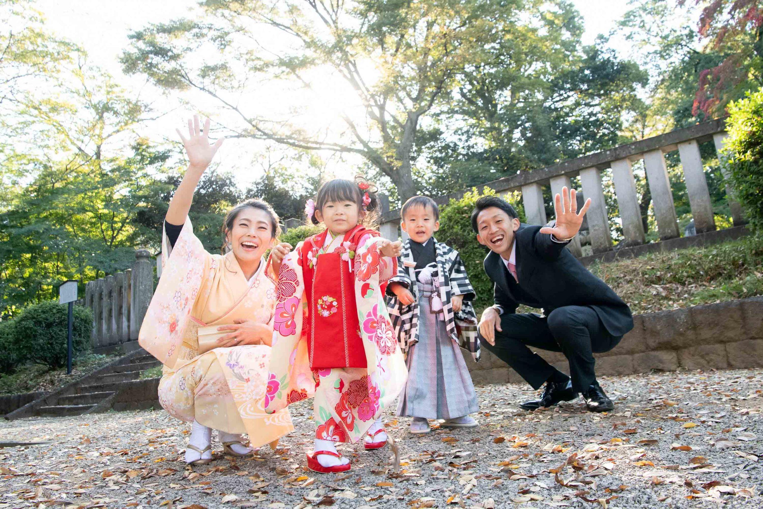 座って葉っぱを投げる七五三の3歳の男の子と女の子と横にいる母と父