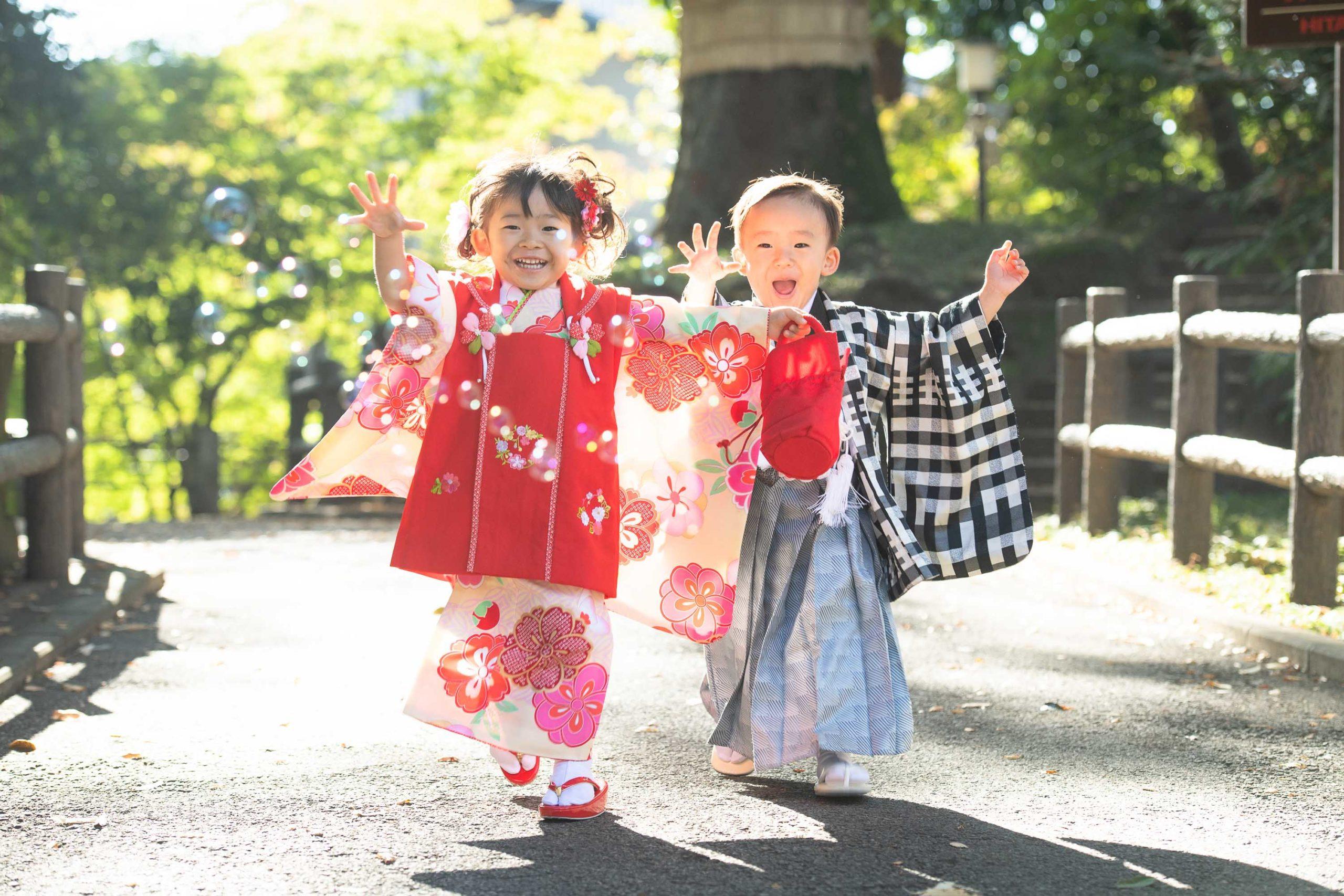 着物を着た3歳の男の子と女の子がシャボン玉を追いかけて走ってくる