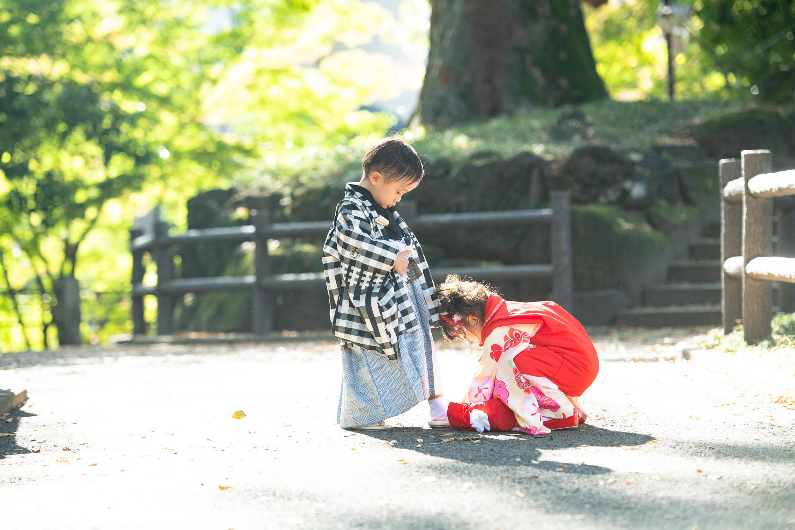 草履の崩れを直してあげる小さな女の子と男の子
