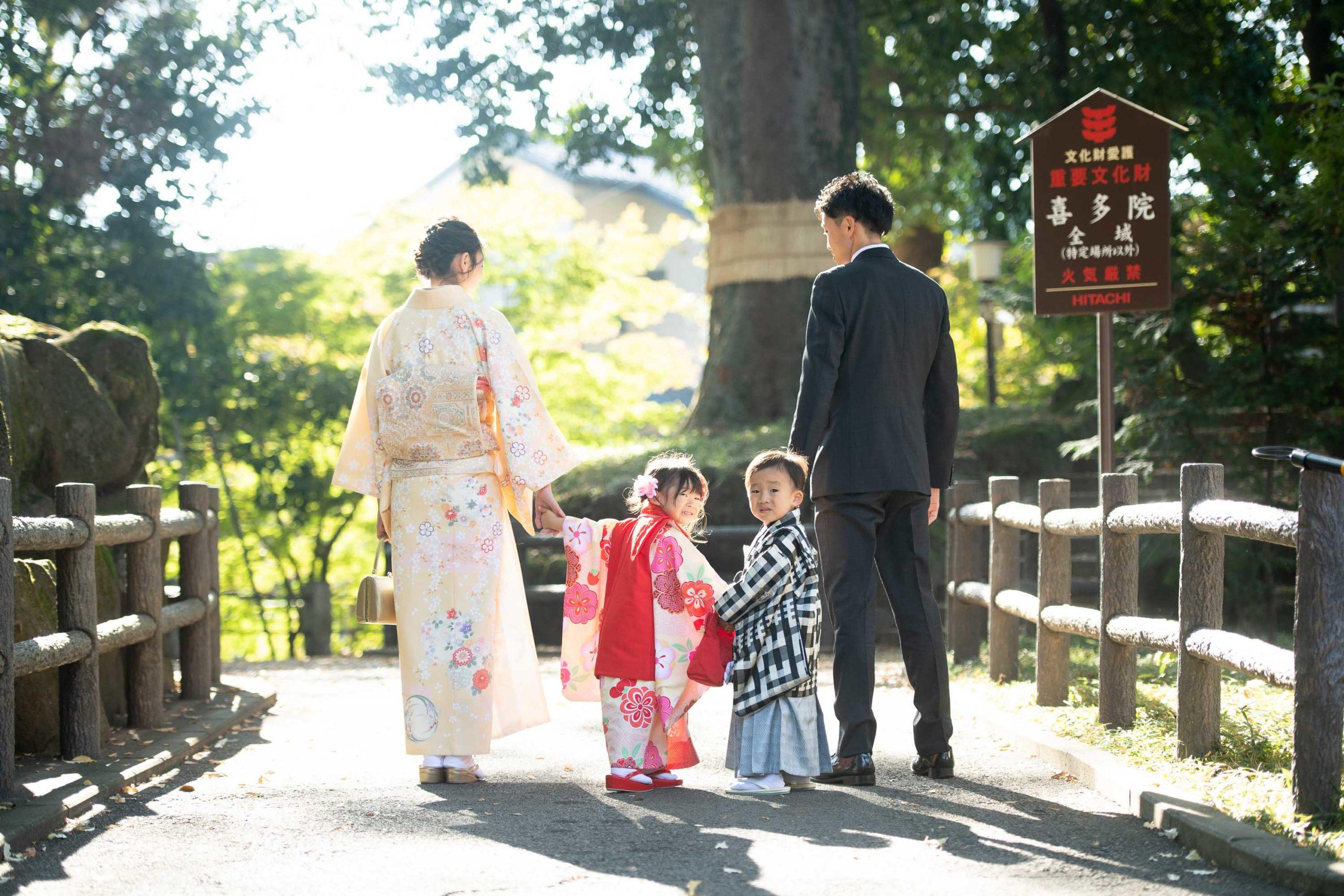 着物を着た3歳の男の子と女の子が母と父に手を繋がれて立っている